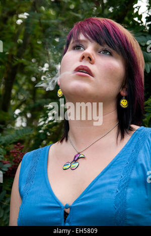 A woman wearing a blue summer dress smoking a cigarette inside the Botanical Gardens in Dundee,UK - Stock Photo