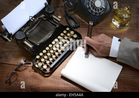 Closeup of a writer at his desk with a typewriter, rotary telephone, glass of whiskey and a cigar. A vintage feel - Stock Photo