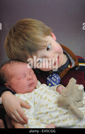 A big brother meets his newborn little baby brother for the first time in hospital - Stock Photo