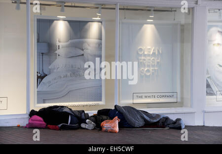 Brighton UK 6th March 2015 - Two homeless rough sleepers settled down for the night outside the White Company shop - Stock Photo