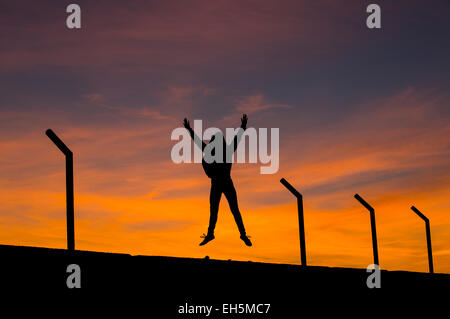 A young woman silhouetted against an orange sunset, jumping into the air with her arms raised. - Stock Photo
