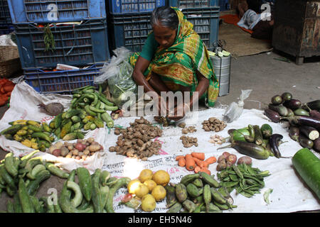 Dhaka, Bangladesh. 7th March, 2015. A Bangladeshi female vegetable vendor waits for customers at a Kitchen market - Stock Photo
