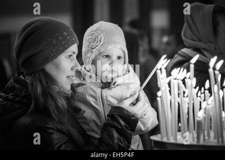 Mother and her little blond Caucasian daughter with candles in Orthodox Russian Church. Black and white photo - Stock Photo
