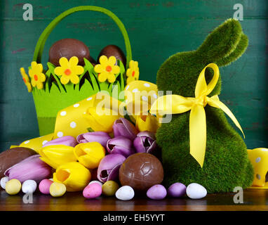 Happy Easter green moss grass bunny rabbit with basket of chocolate eggs and spring tulips against a green wood - Stock Photo