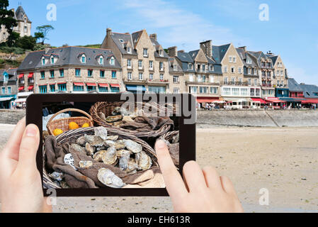 travel concept - tourist taking photo of waterfront of town Cancale in summer day. This town is 'oyster capital' - Stock Photo
