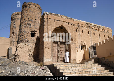 Man in carved wood doorway of old mudbrick building, Al-Mudayrib, Oman - Stock Photo