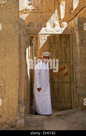 Man in doorway of old mudbrick building, Al-Hamra, Oman - Stock Photo