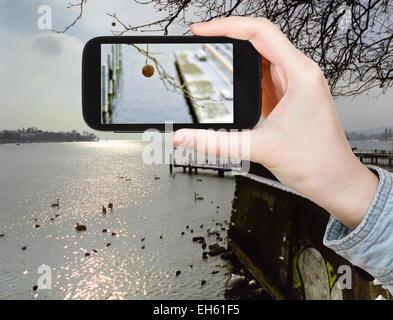 travel concept - tourist taking photo of Lake Geneva in winter on mobile gadget, Switzerland - Stock Photo