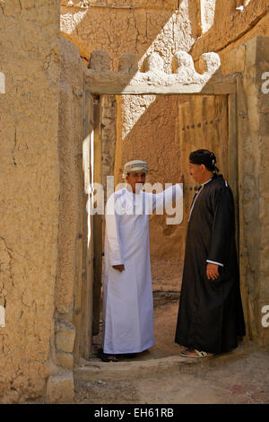 Men in doorway of old mudbrick building, Al-Hamra, Oman - Stock Photo
