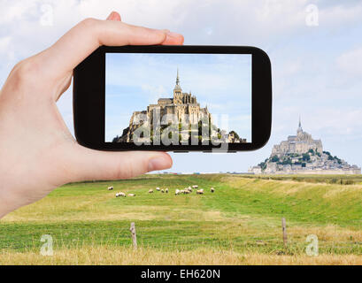 travel concept - tourist take photo of mont saint-michel abbey, Normandy, France on mobile gadget - Stock Photo