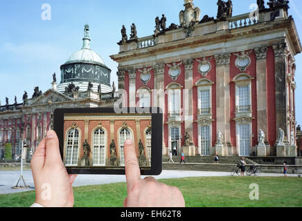travel concept - tourist taking photo of statues of New Palace in Sanssouci Royal Park, Potsdam on mobile gadget, - Stock Photo