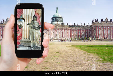 travel concept - tourist taking photo of scupture of New Palace in Sanssouci Royal Park, Potsdam on mobile gadget, - Stock Photo