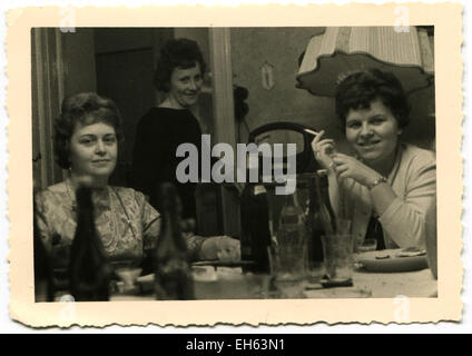 Berlin, Germany. 7th Mar, 2015. CIRCA 1960s: Three women posing at the festive table, on which stand the bottle - Stock Photo