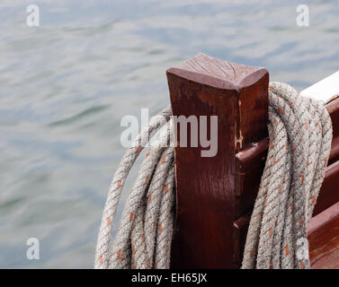 Coiled rope hung on wooden post on boat. - Stock Photo