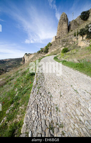 Rural cobbled road on hill slope between meadows in Andalusia countryside, Spain. - Stock Photo