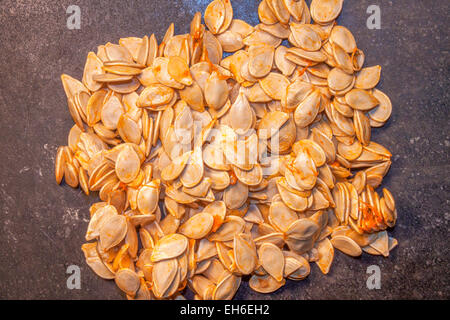 A lot of pumpkin seed, on a stone plate - Stock Photo