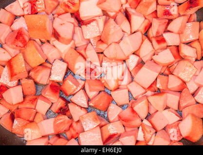 A lot of fried sausage dice, on a frying pan - Stock Photo