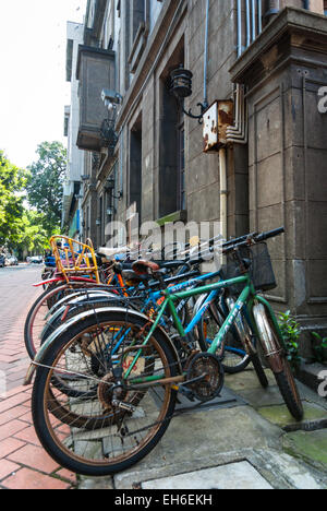Old bicycles against French colonial building on Shamian Island, Guangzhou, China - Stock Photo