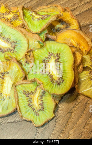 A pile of dry kiwis, on wooden background - Stock Photo