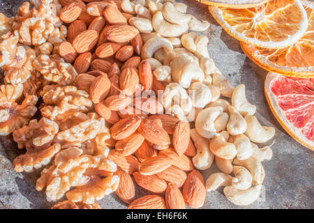 Walnuts, cashew nuts and almonds, on a stone plate - Stock Photo