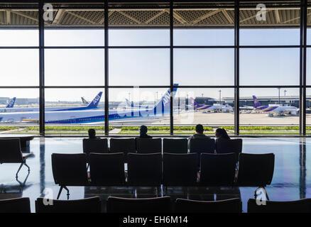 People seated in Narita Terminal 1, looking through large glass windows over the terminal gates at Narita International - Stock Photo