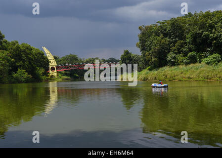 Man rows inflatable raft toward a gate at the campus of University of Indonesia in Depok, West Java. - Stock Photo