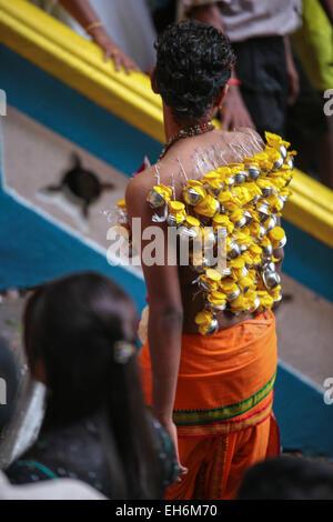 Hindu pilgrims with milk pot kavaldi climbing the Batu Cave temple staircase, Malaysia during Thaipusam festival - Stock Photo