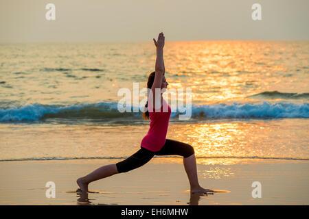 beautiful girl doing yoga near the ocean barefoot - Stock Photo