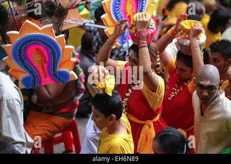 Hindu female pilgrims carrying milk pot kavaldi climbing Batu Cave temple, Malaysia during Thaipusam festival on - Stock Photo
