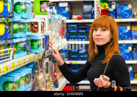 girl in shop chooses Christmas decorations - Stock Photo