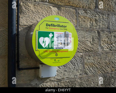 Wall mounted heart defibrillator life saving equipment for cardiac arrest with code lock for public use. England - Stock Photo