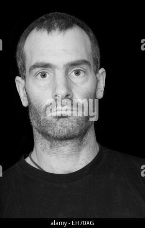 black and white portrait of a rugged grizzled middle aged man with black t-shirt on black background - Stock Photo
