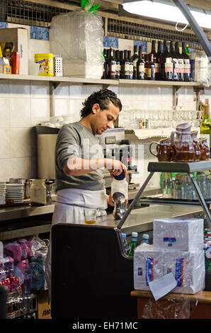 A man prepares coffee at a restaurant in Le Marché des Enfants Rouges, an organic marketplace in Paris. - Stock Photo