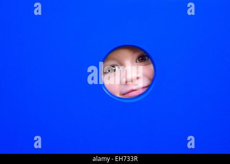 cute little boy's face peeking through a hole of a playground equipment. - Stock Photo