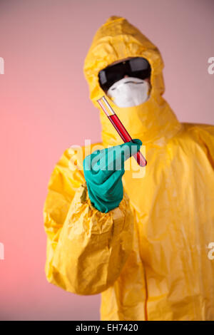 Laboratory man in chemical protective dress holding vial of blood sample - Stock Photo