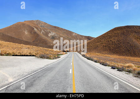 Road stretching out into the distance at Lindis Pass in New Zealand - Stock Photo