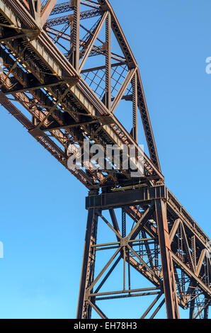 Section of Rusty Steel Girder Railroad Bridge in Bright Daylight with Clear Blue Sky Background. - Stock Photo