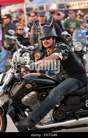 A leather clad biker with animal horns on his helmet cruises down Main Street during the 74th Annual Daytona Bike - Stock Photo