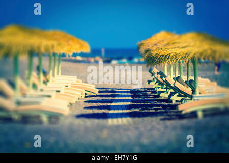 Sunloungers and parasols on a beach - Stock Photo
