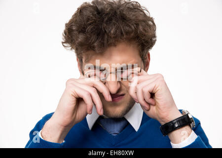 Young businessman rubbing his eyes over white background - Stock Photo