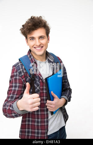Happy male student with backpack and folders showing thumb up - Stock Photo