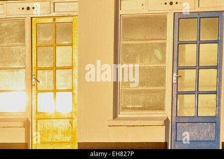 Yellow and blue beach hut doors in bright dawn sunlight Porthgwidden Beach St Ives Cornwall England Europe