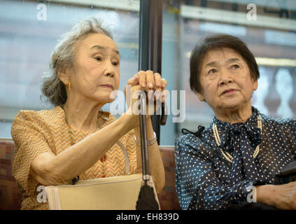 Two well-dressed elderly Japanese ladies on a train in Tokyo. Senior citizens in Japan; old Japanese people; elderly - Stock Photo
