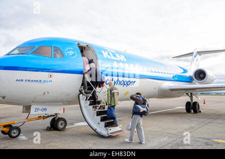 Passengers climb aboard a Fokker F70 operated by KLM Cityhopper on a short flight from Liverpool AIrport, UK. - Stock Photo