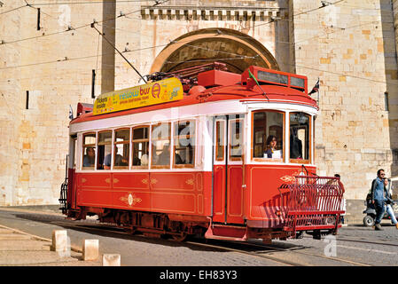Portugal, Lisbon: Nostalgic tramway with tourists passing the medieval cathedral in historic Alfama - Stock Photo