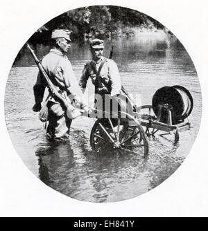 In this photo, Austrian soldiers are shown laying a field telephone line across a stream during World War I—in late - Stock Photo