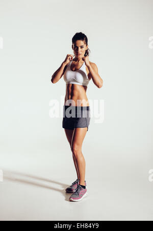 Strong young woman doing boxing exercising in studio. Image of fit young female boxer against grey background. - Stock Photo