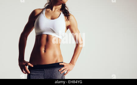 Close up of fit woman's torso with her hands on hips. Female with perfect abdomen muscles on grey background with - Stock Photo