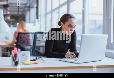 Image of woman using laptop while sitting at her desk. Young african american businesswoman sitting in the office - Stock Photo