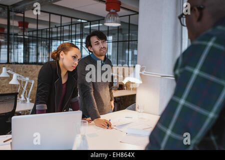 Business people standing besides a table working on new creative ideas. Diverse team of young professionals in a - Stock Photo